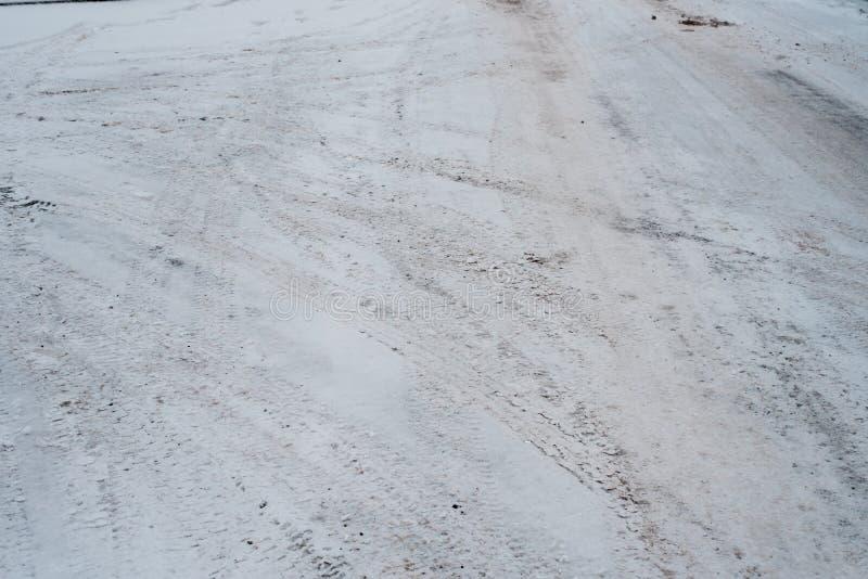 在冬天,汽车踪影从在交叉点把雪引入在城市, 白色和肮脏的雪 免版税库存照片