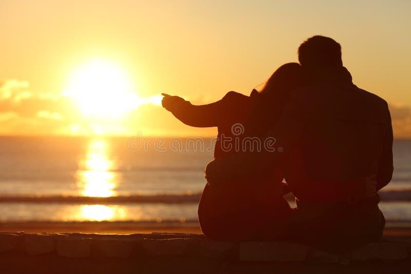 在冬天结合享受在海滩的日落 库存图片