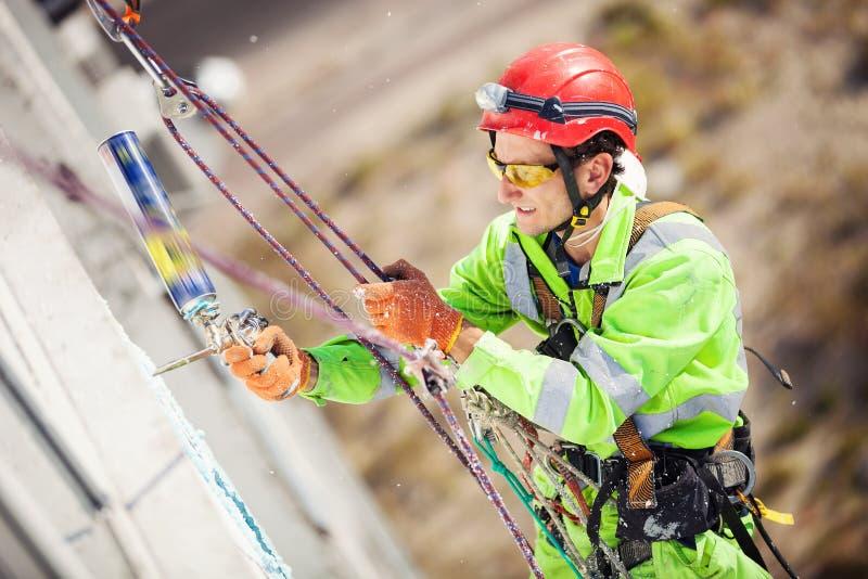 在冬季化工作期间的工业登山人 免版税库存图片