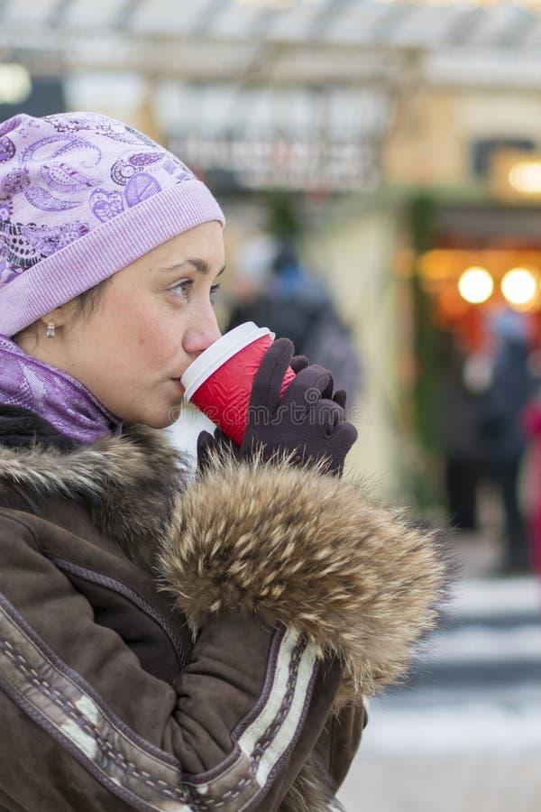 在冬季衣服街道的美女饮用的咖啡  时髦的微笑的妇女画象冬季衣服喝的热 库存图片