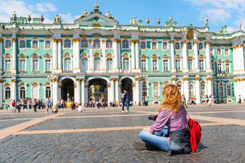 在冬宫前面的年轻女性游人在圣彼得 免版税库存图片