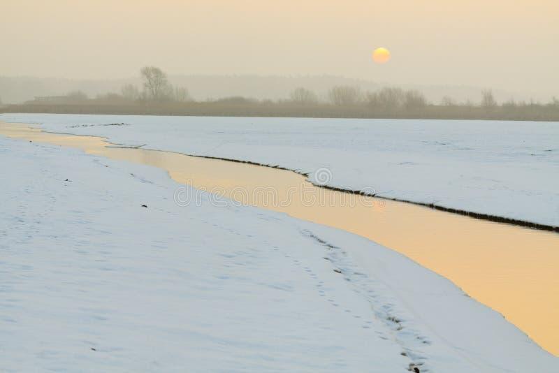 在冬时的小流动的小河 免版税库存图片