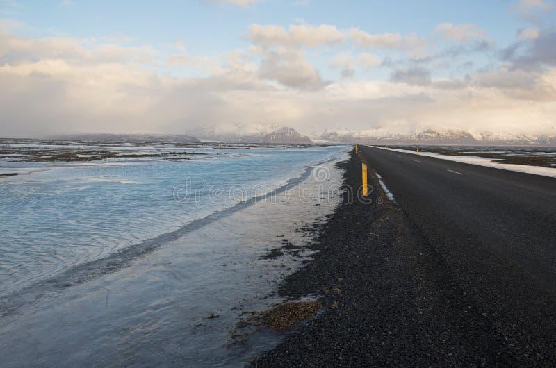 在冬时的主路与在边缘的大海,冰岛 图库摄影