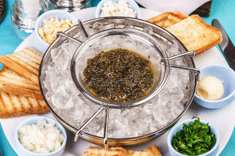 在冰、多士、黄油、绿色和一套的地中海鱼子酱开胃菜调味汁 库存照片