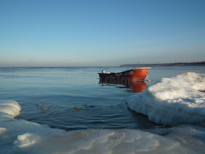 在冰冷的海停泊的红色小船 相互的W 免版税库存照片
