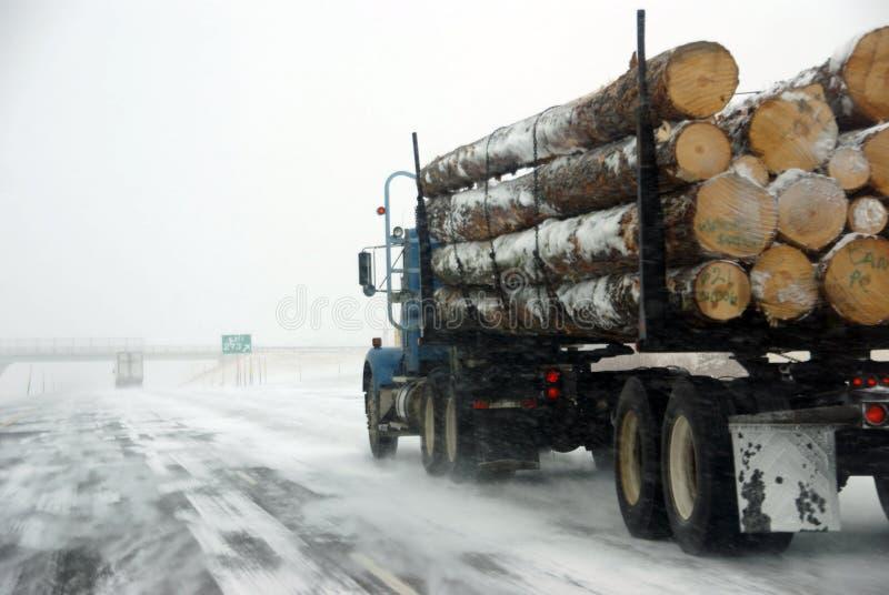 在冰冷的路的记录的卡车 免版税库存照片