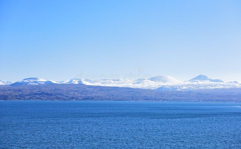 在冰和雪下的蓝色湖 免版税库存图片