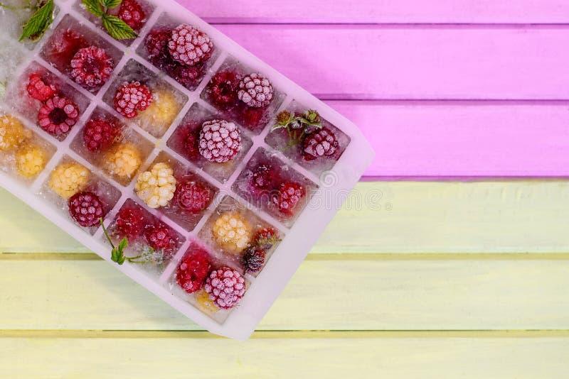 在冰块的冷冻红色和黄色莓在木背景 免版税库存照片