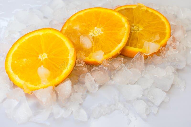 在冰的三个水多的橙色切片 免版税库存照片