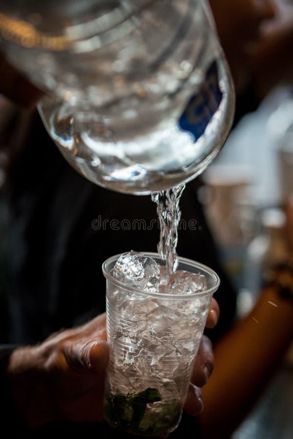 在冰的倾吐的饮料到在酒吧的一清楚的塑料杯里 库存照片