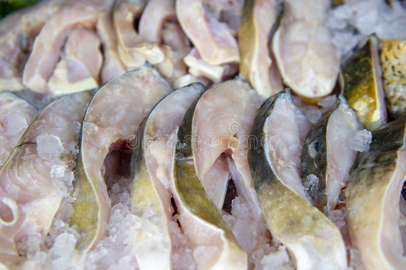 在冰的鲶鱼切片在市场卖主桌上 免版税库存照片