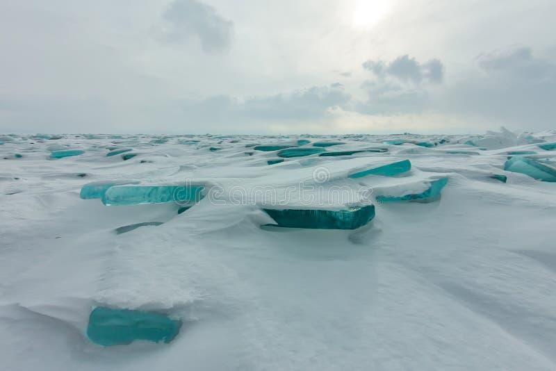 在冰破晓贝加尔湖蓝色小丘在一个多雪的领域的,在旅途上的冬天 库存照片