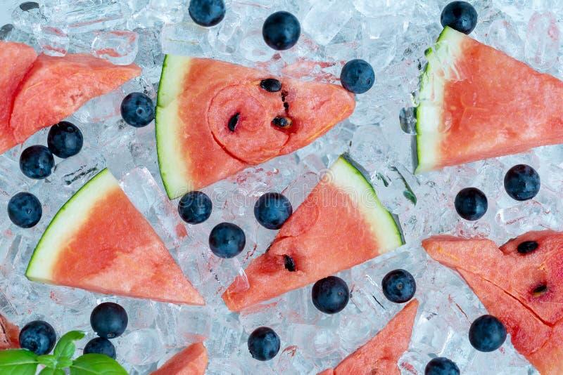 在冰管背景的西瓜切的和蓝莓 免版税库存照片