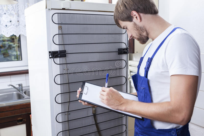 在冰箱修理期间的杂物工 免版税图库摄影