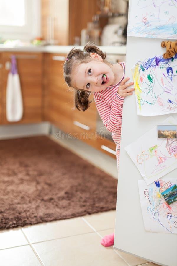 在冰箱门后的逗人喜爱的小女孩口香糖在厨房里 库存图片