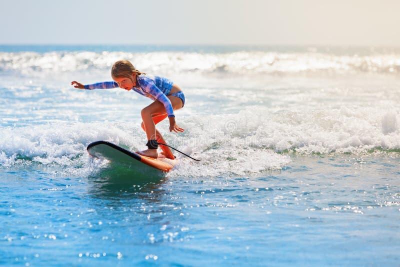 在冲浪板的年轻冲浪者乘驾有在海的乐趣的挥动 免版税库存照片