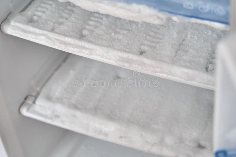 在冷冻机的冰 冰冷却的管 冰箱要求除霜 冷冻机的修理 空的冰箱,许多在的冰 免版税库存图片