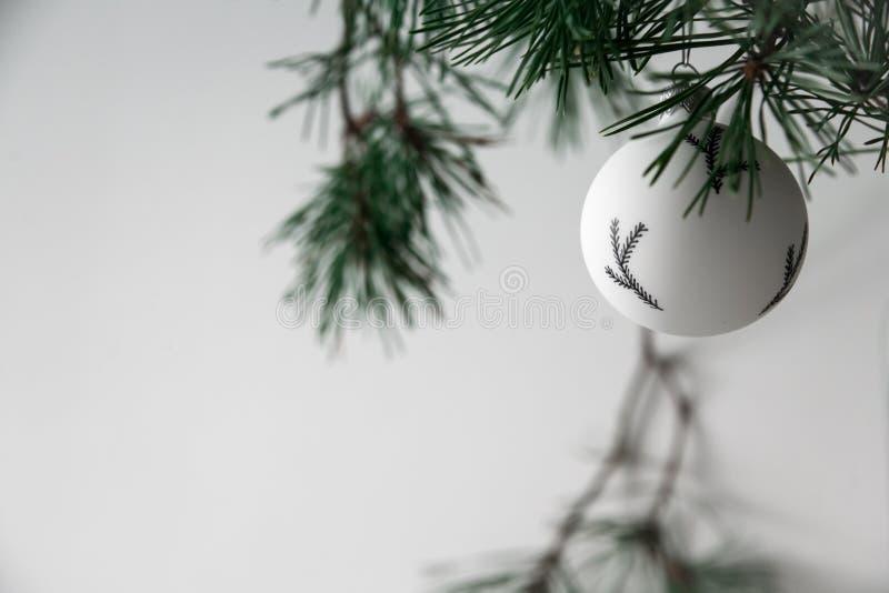 在冷杉分支中的圣诞节黑白玩具 免版税库存照片