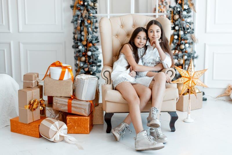 在冷杉木前面的女孩孪生 新年` s伊芙 圣诞节 在冷杉木的舒适假日与光 免版税图库摄影