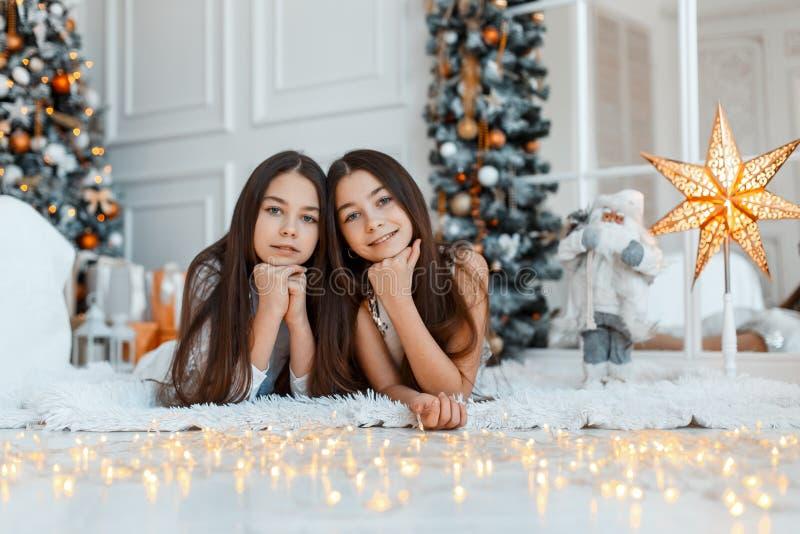 在冷杉木前面的女孩孪生 新年` s伊芙 圣诞节 在冷杉木的舒适假日与光 免版税库存照片