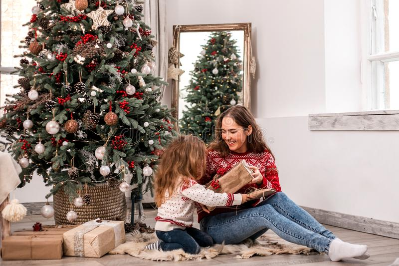在冷杉木附近的愉快的母亲和女儿就座 库存照片