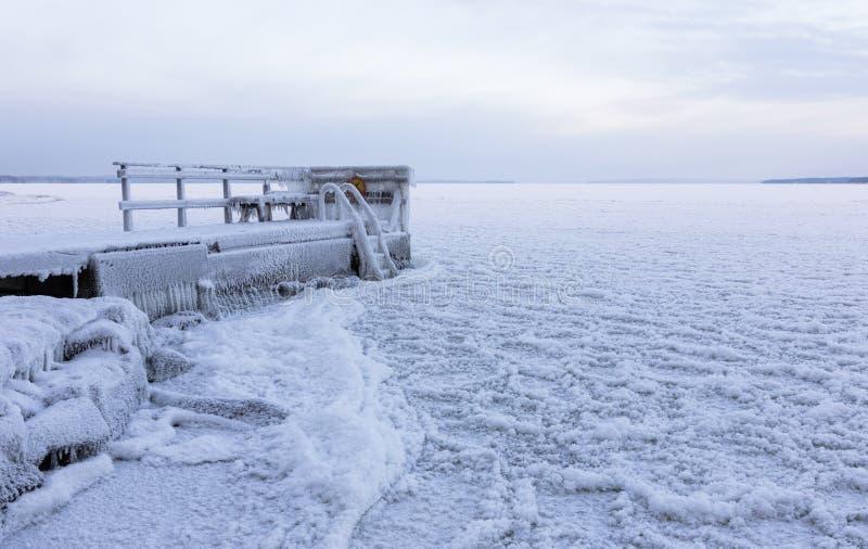 在冷漠的湖旁边的冻码头 免版税库存图片