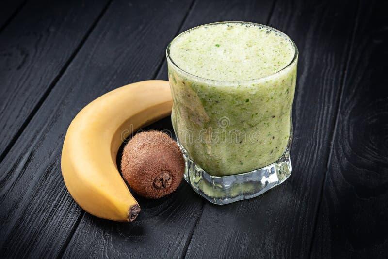 在冷玻璃杯的接近的看法与圆滑的人用菠菜、香蕉和猕猴桃 戒毒所programm 在玻璃的新戒毒所绿色饮料 图库摄影
