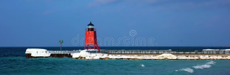 在冷的冬天期间,红色灯塔在冻湖 免版税库存图片