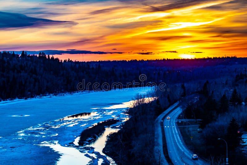 在冻冬天河的美好的金黄日落 库存照片