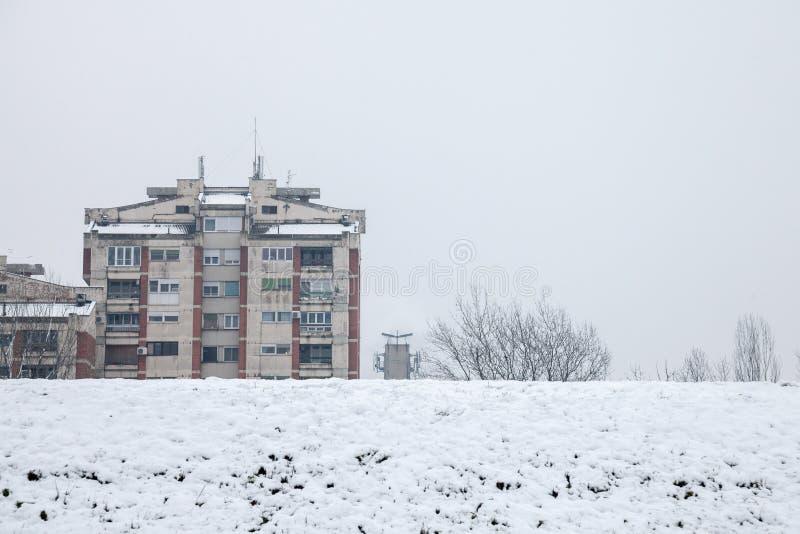 在冻小山前面的共产主义房屋建设在潘切沃,塞尔维亚,在与雪的一个下午期间 库存照片
