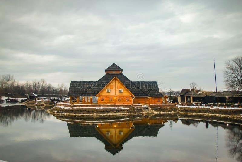 在冻池塘附近的木餐馆日落的,冬天阴天 库存照片