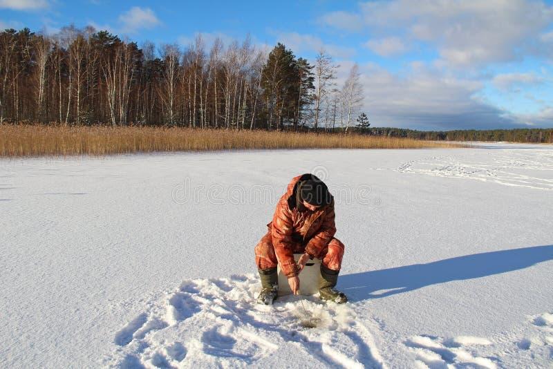 在冻湖的冬天渔在阳光天 渔夫在湖的冰钓鱼 免版税库存照片