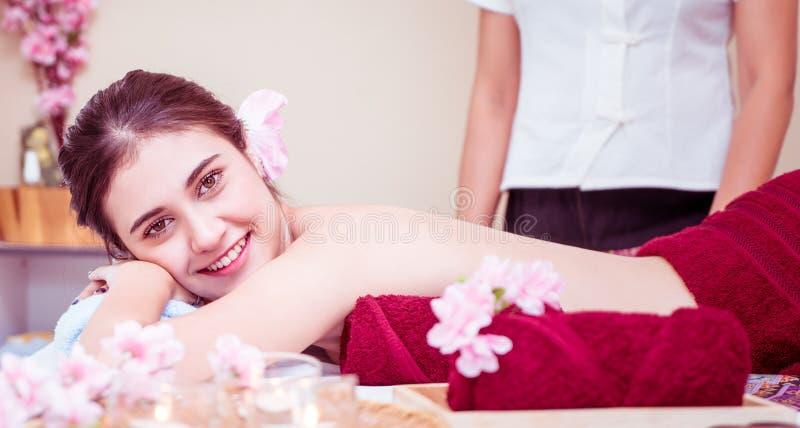 在准备好温泉的床上的赤裸妇女得到按摩 库存照片