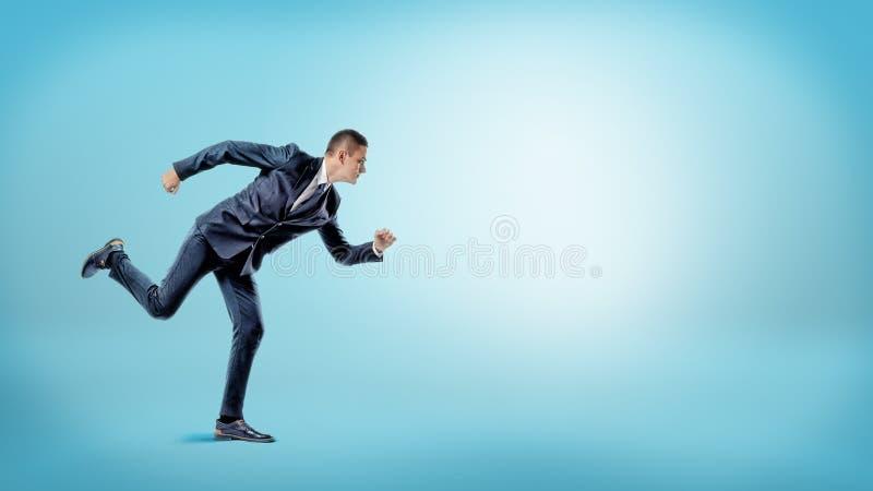在准备好赛跑者的位置的一个商人开始在蓝色背景 新的商业 免版税库存照片