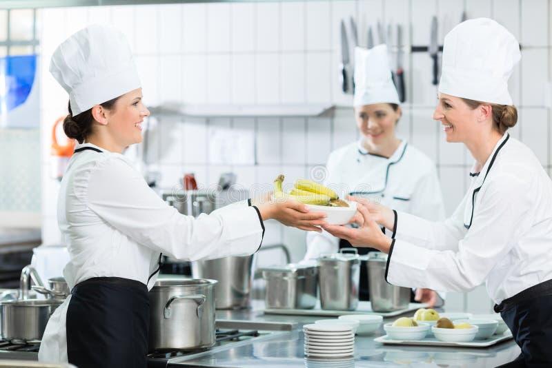 在准备盘的军用餐具的厨房职员 免版税库存图片