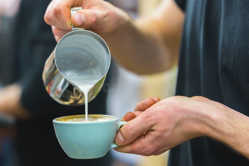 在准备适当的热奶咖啡的咖啡馆的Barista倒生泡沫的牛奶入咖啡,做拿铁艺术,样式 图库摄影