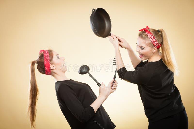 在减速火箭的女孩之间的厨房战斗 库存照片