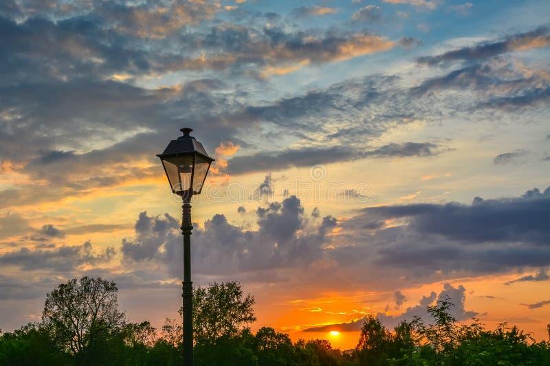 在减速火箭的样式的灯笼在五颜六色的日落的背景 免版税图库摄影
