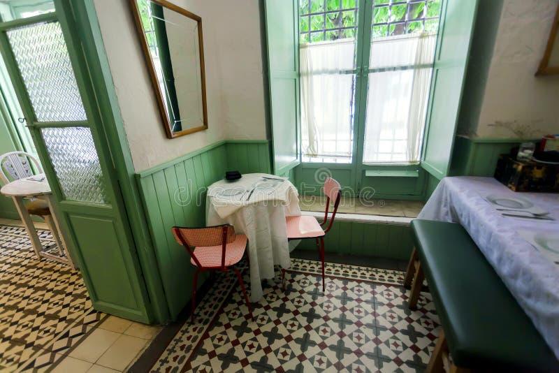 在减速火箭的样式餐馆里面的Dinning房间有窗口、葡萄酒细节和服务的访客的 免版税库存照片