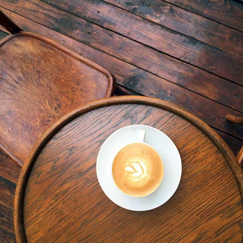 在减速火箭的桌上的平的加奶咖啡 免版税库存照片