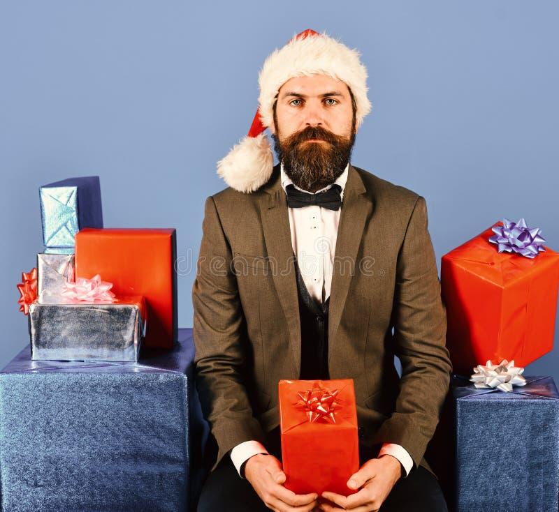 在减速火箭的衣服的圣诞老人提出蓝色和红色礼物 库存图片