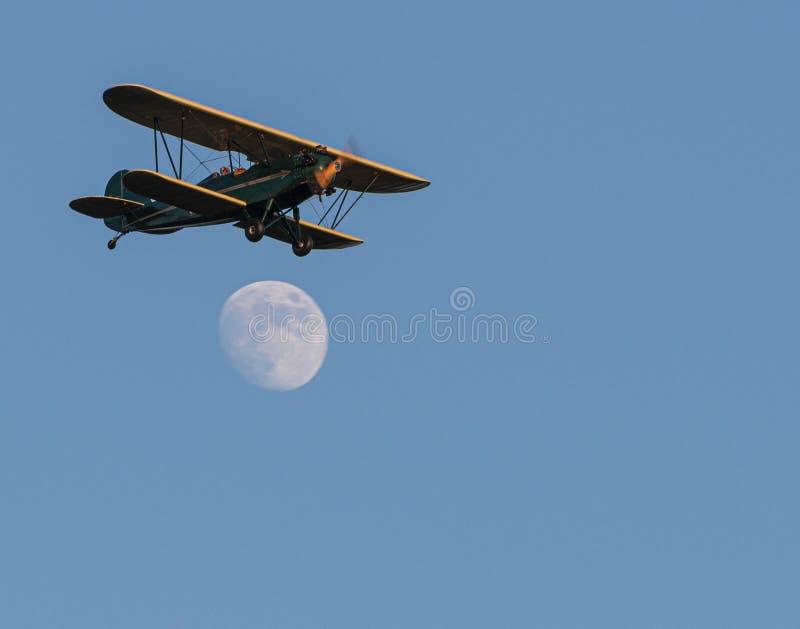 在几乎满月的绿色和黄色双翼飞机飞行 库存照片