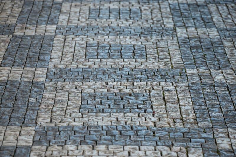 在几何样式安置的更加黑暗和更加明亮的大卵石石头在布拉格老镇 免版税图库摄影