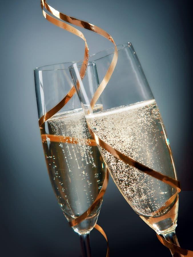 在凹槽玻璃的酒与金鞋带设计 图库摄影