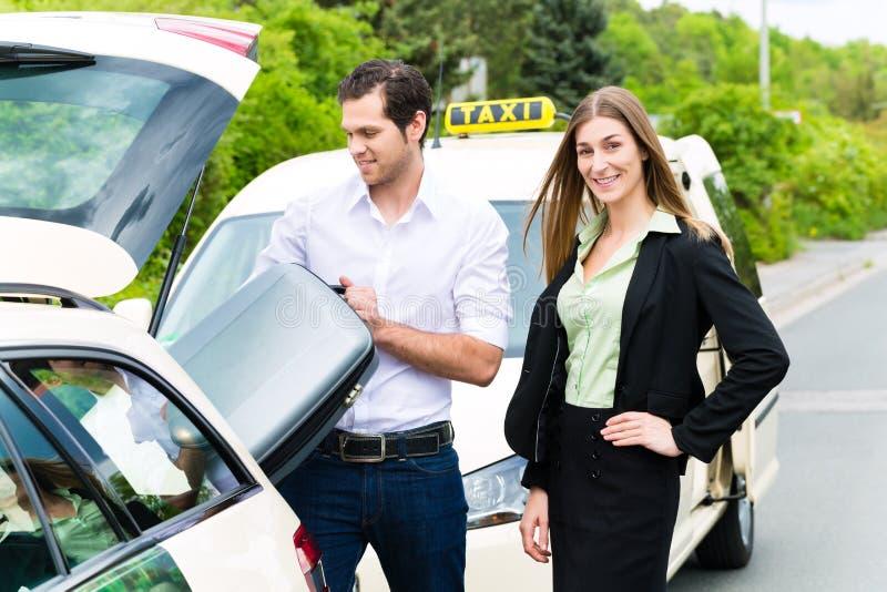 在出租汽车前面的年轻女实业家有行李的 免版税库存照片