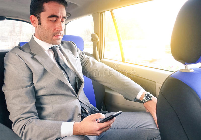 在出租车的年轻商人和与智能手机的短信的sms 库存照片