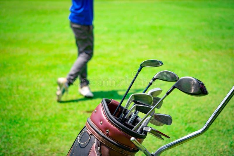 在击中高尔夫球的袋子推车和被弄脏的高尔夫球运动员的高尔夫俱乐部衣服 库存照片