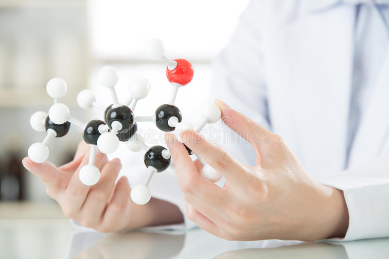 在分子模型的亚洲女性科学家老师点解释 免版税库存照片