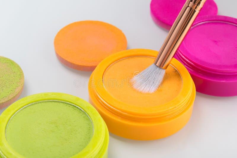 在分开的箱子的鲜绿色,橙色和桃红色眼影膏有刷子的,隔绝在白色 库存图片