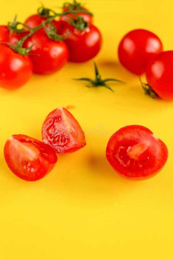 在分支和切好的蕃茄的成熟新鲜的水多的有机西红柿在黄色塑料切板 r 库存图片